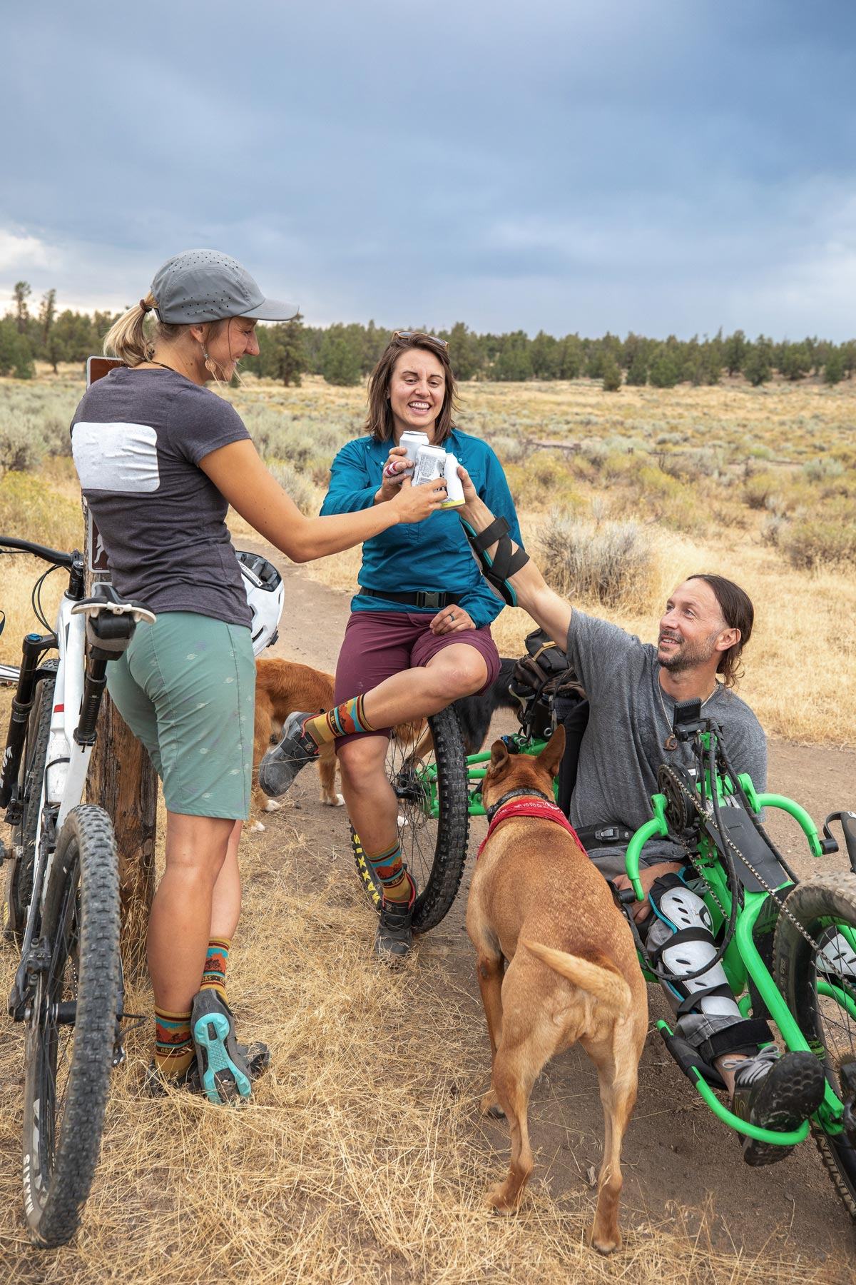 photo of group of mountain bikers, one riding an adaptive offroad handcycle.
